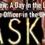 """A black sign hanging from the side of a building with the work 'Ask' in yellow letters with the title """"Interview: A Day in the life of a police officer in the UK"""" in white lettering a police officer in the UK"""